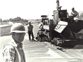 B/w photo of man in hard hat, with construction crew in background