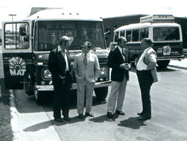 4 legislators in front of buses (b&w)