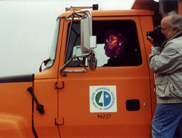 Woman driving truck with cameraman on runninboard