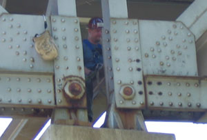 An inspector with a contracting firm observes gusset repair work on the Hwy 43 bridge in Winona. Photo by Craig Falkum