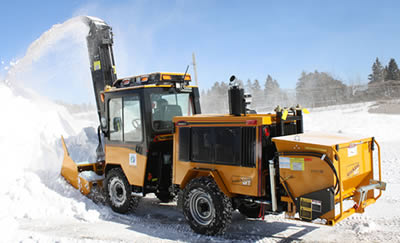 Trackless machine clearing snow