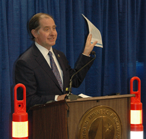 Commissioner Charlie Zelle waving funding chart at news conference
