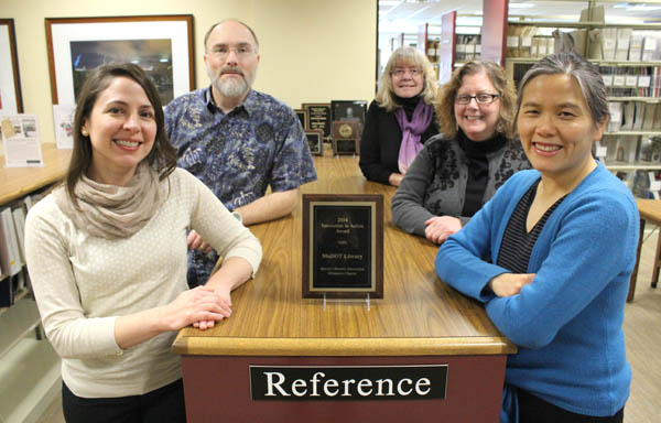 4 women, 1 man standing in library by award