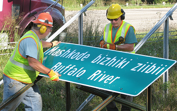 Photo of District 4 sign crew putting up dual language sign.