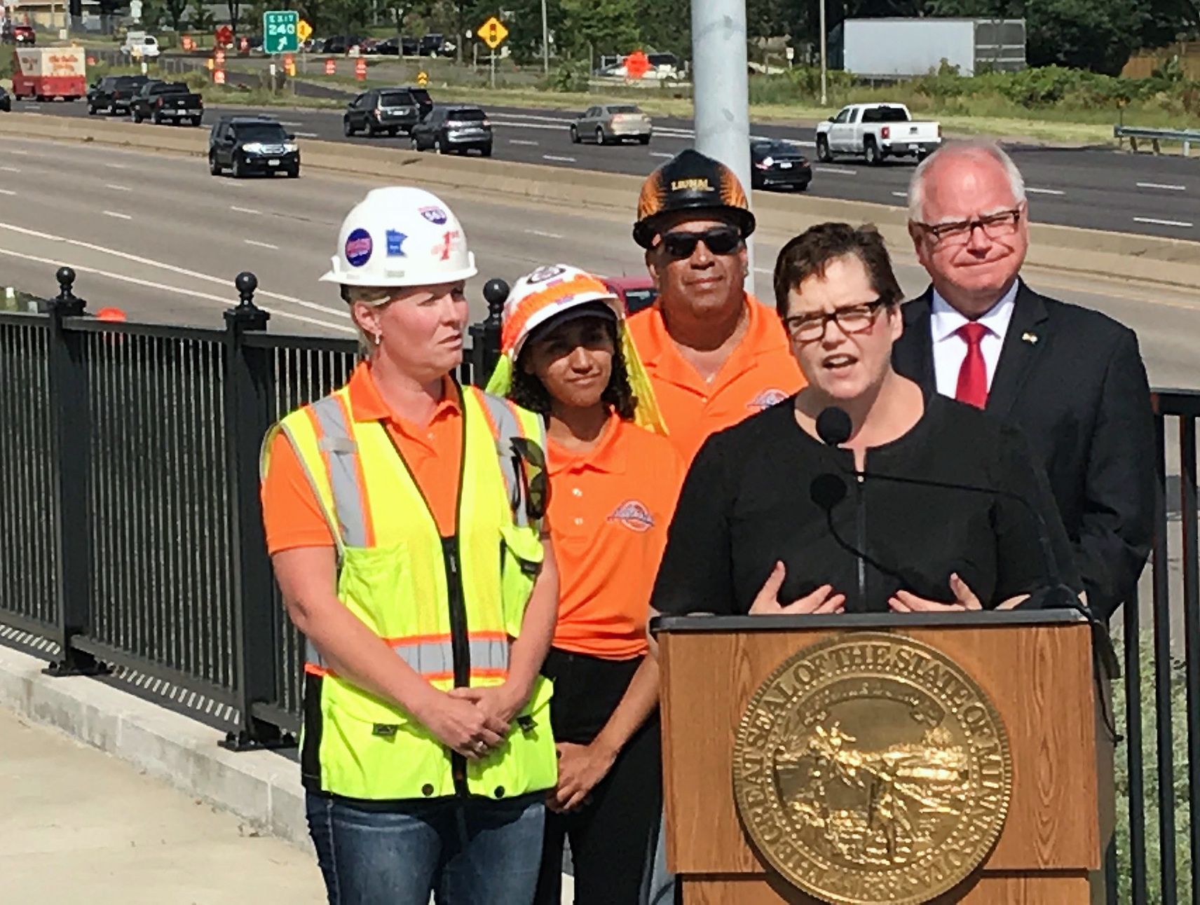 Commissioner maragaret anne kelliher speaking at a podium. Gov. tim walz is to her left, three other people are two her right, and a busy section of freeway is behind her.