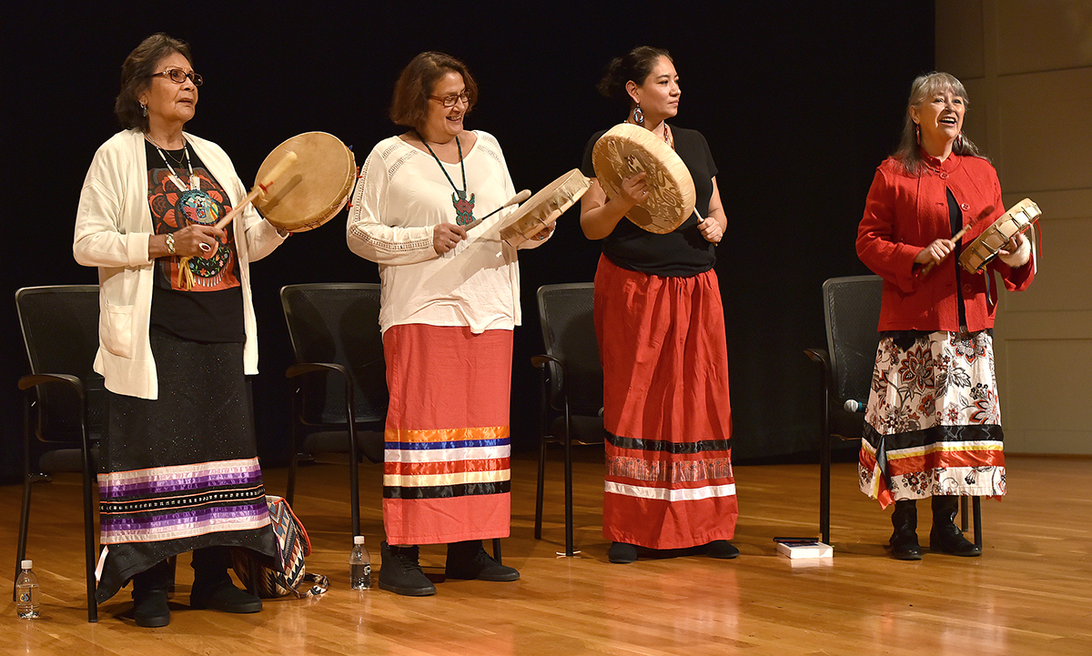 Photo: four women drumming on a stage