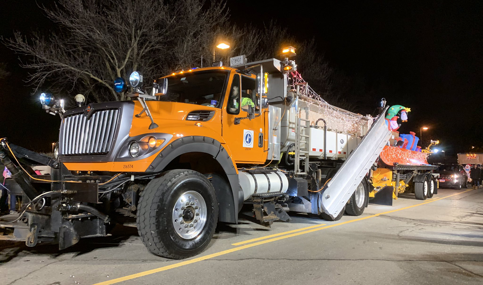 Photo: a MnDOT snowplow covered in twinkling holiday lights