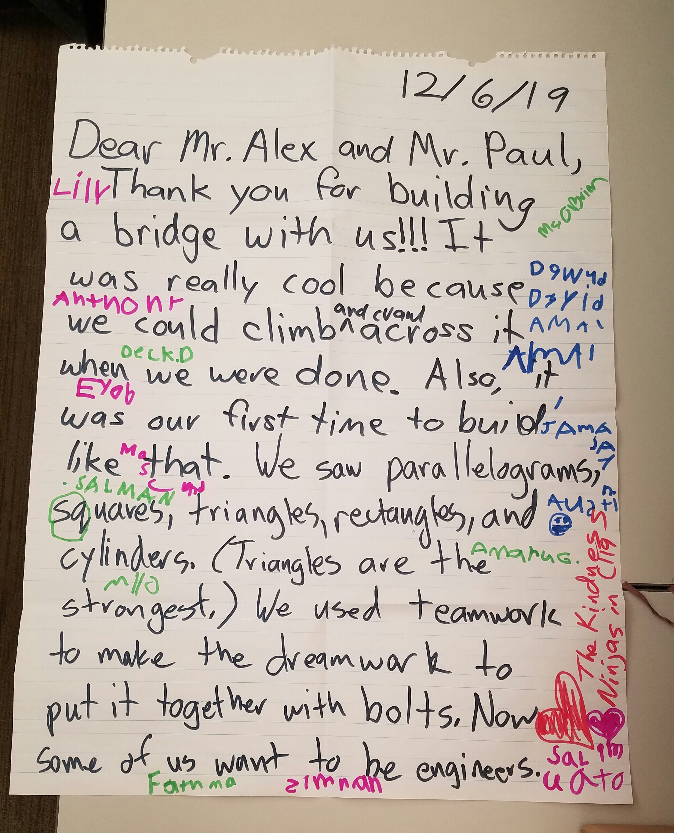 Photo: thank-you note in children's handwriting which says dear mr alex and mr paul, thank you for building a bridge with us. It was really cool because we could climb and crawl across it when we were done. Also, it was our first time to build something like that. We saw paralellograms, squares, triangles, rectangles and cylinders. Triangles are the strongest. We used teamwork to make the dreamwork to put it together with bolts. Now some of us want to be engineers.