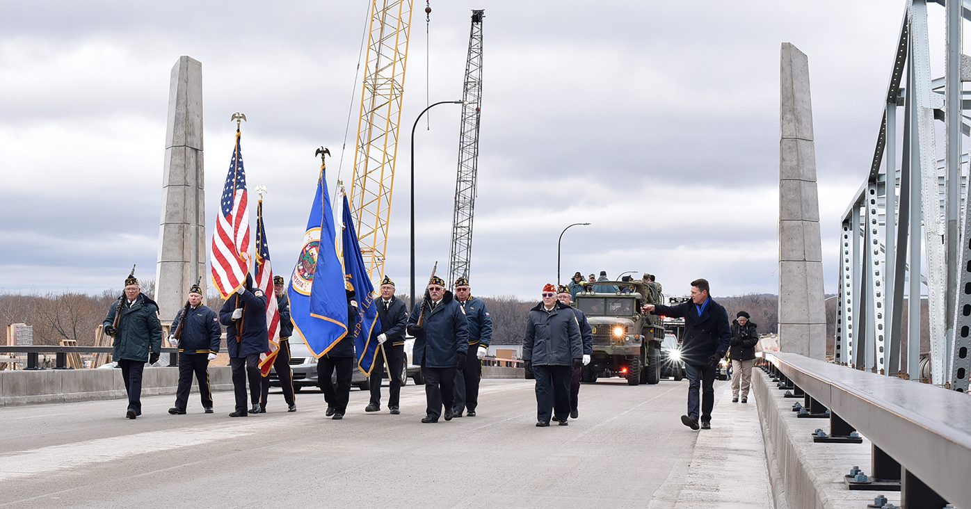 This picture shows a line of men carrying state and U.S. flags in a line while walking across the newly completed bridge. Several vintage military vehicles are behind the men, also crossing