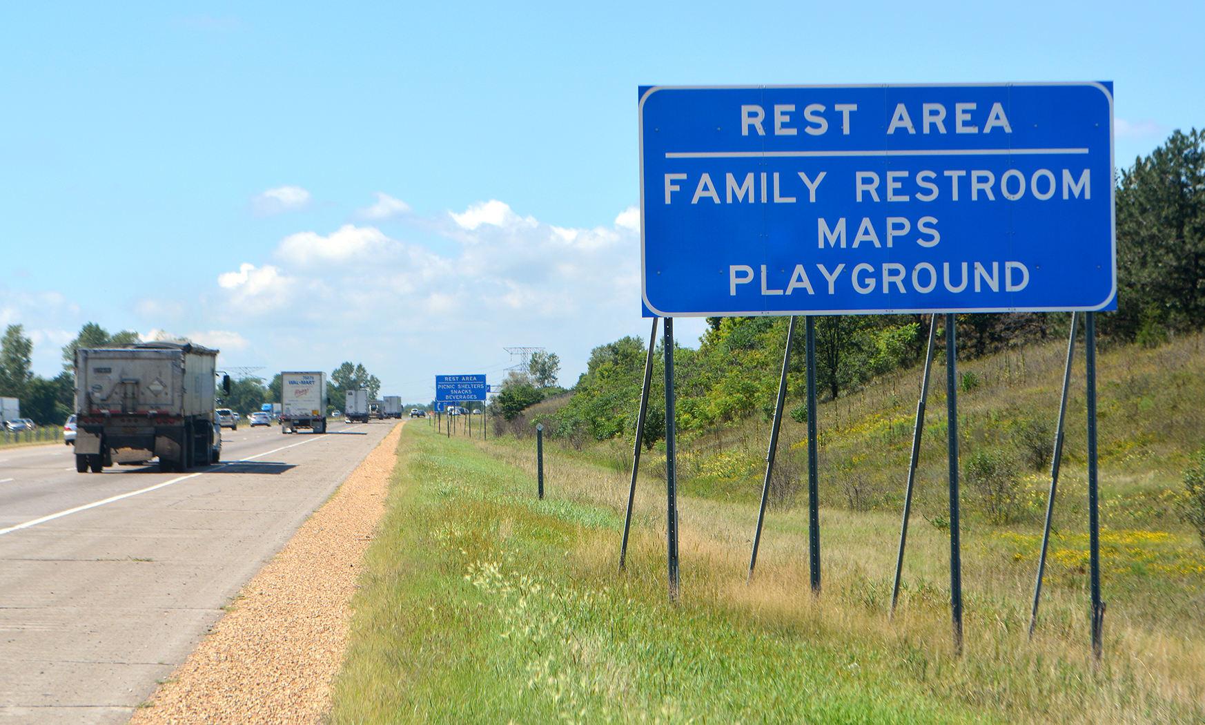 This photo shows a highway sign which has the words Rest Area on the top line, listing ameneties family restroom, maps and playground written underneath that.