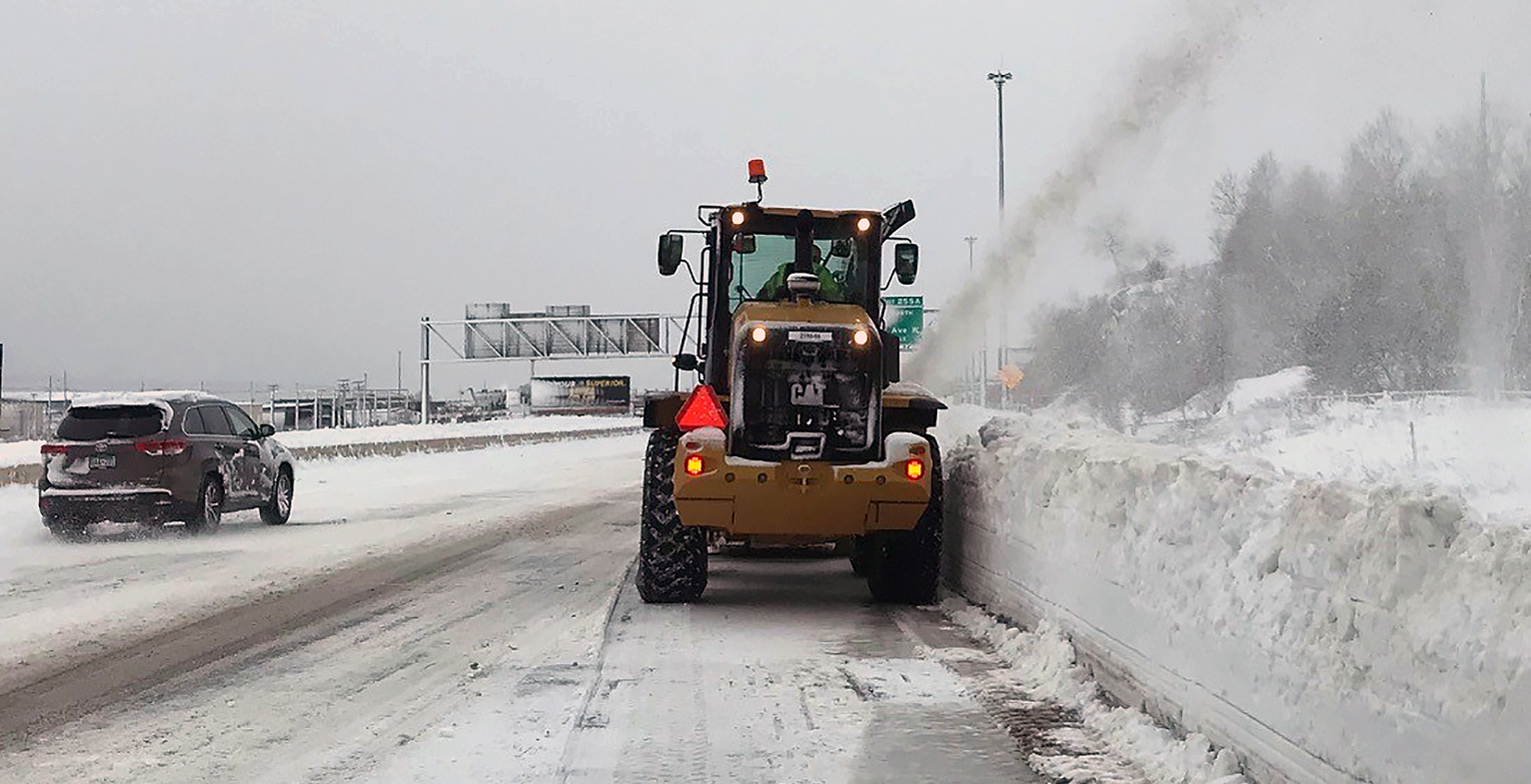 This photo shows a large snowblower blowing snow on the side of I-35. The snow to the right of the blower is close to four feet tall.