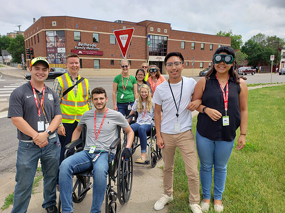 Interns and staff standing at a street corner and looking at the camera. Two interns are in wheelchairs, and one is weaing vision impairment goggles. These devices are meant to simulate what it is like for people with disabilities when they use the street to travel