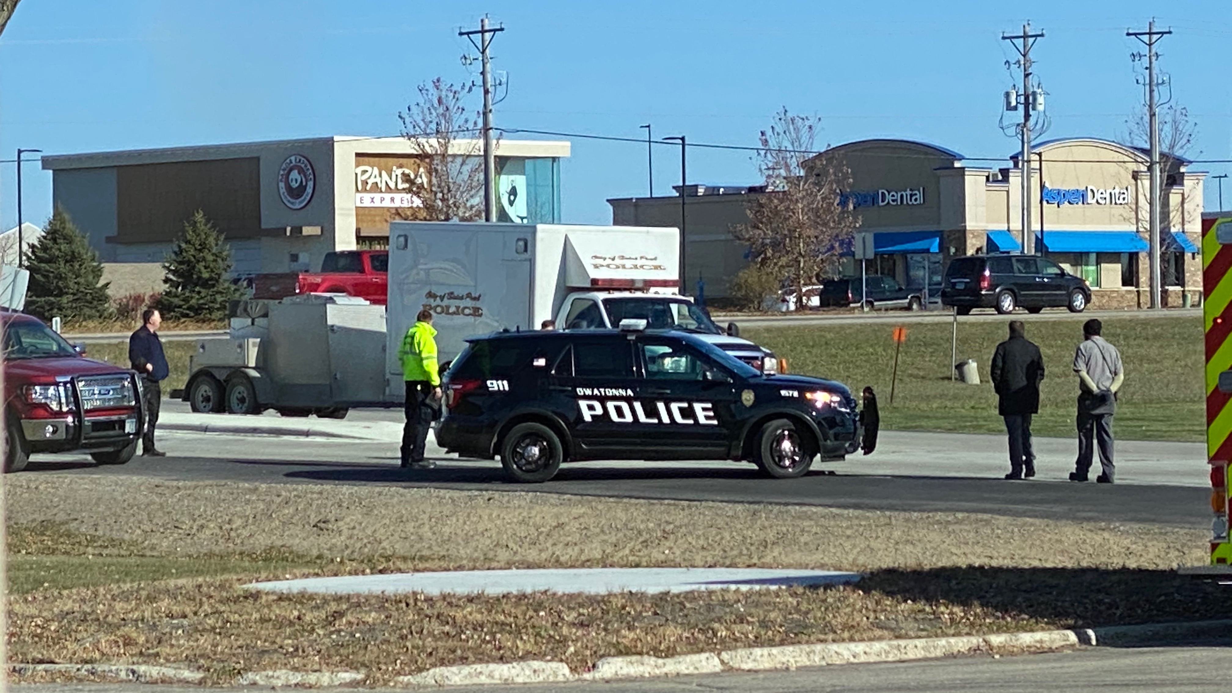 Police vehicles block an intersection near the Owatonna truck statuon, as officers stand by