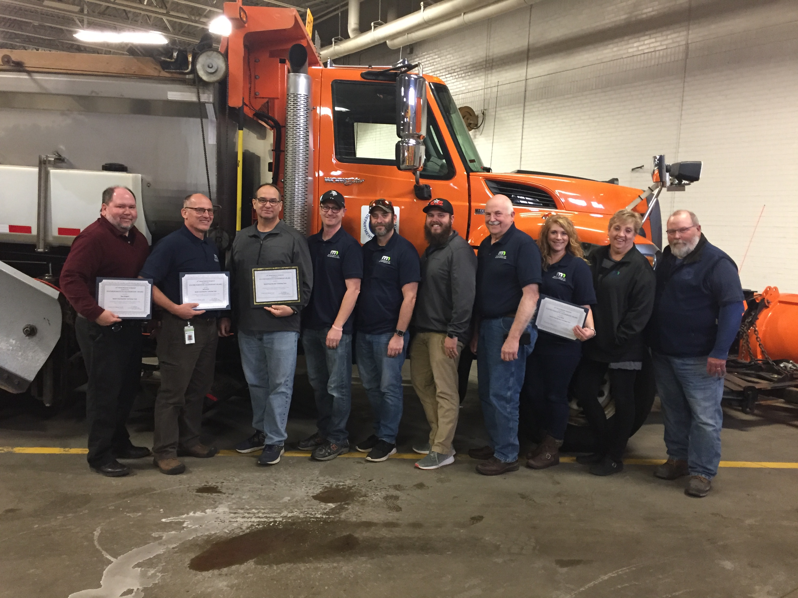 Nine people lined up in front of a plow truck, with four holding certificates