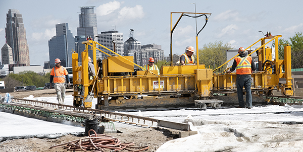 A large yellow machine is being operated by a work crew