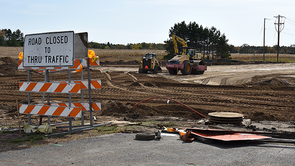 A sign marked road closed to thru traffic sits near an empty stretch of dirt where the road will be