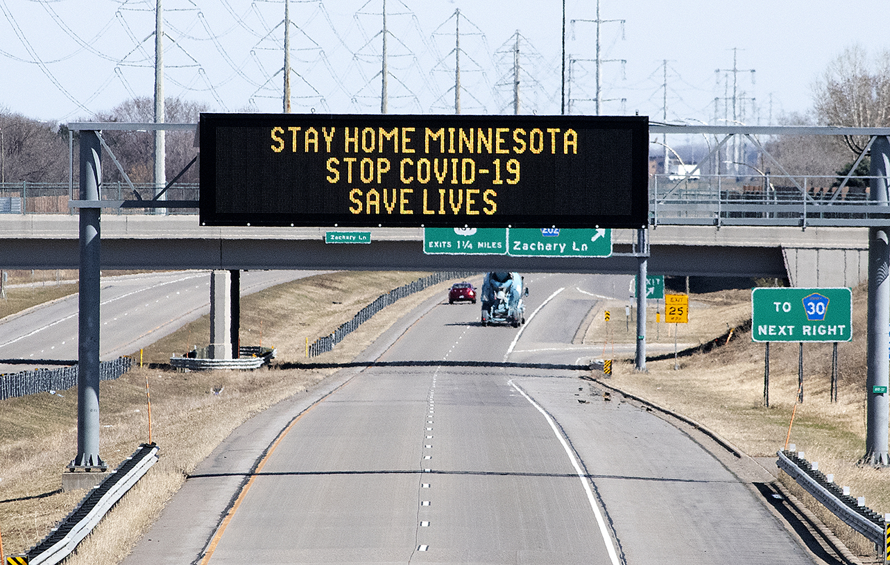 Photo: Electronic sign board displays the message stay home minnesota. Stop COVID 19. Save Lives