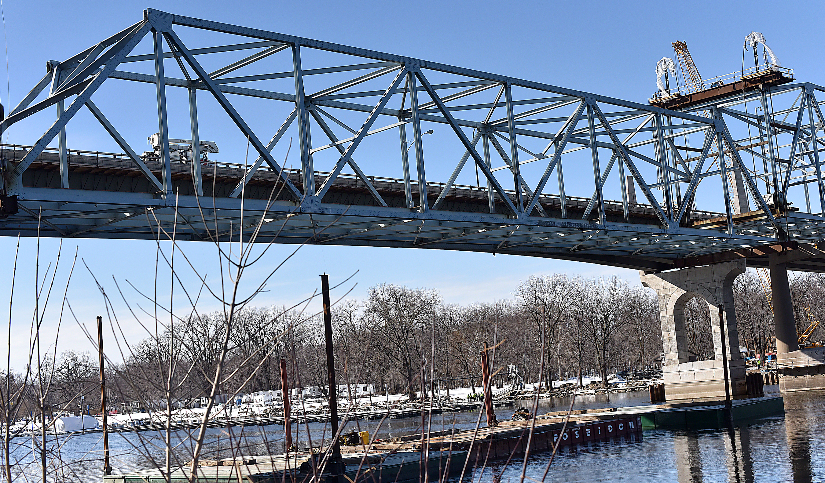 Photo: The steel framework of the bridge's center span is being slowly lowered onto a barge.
