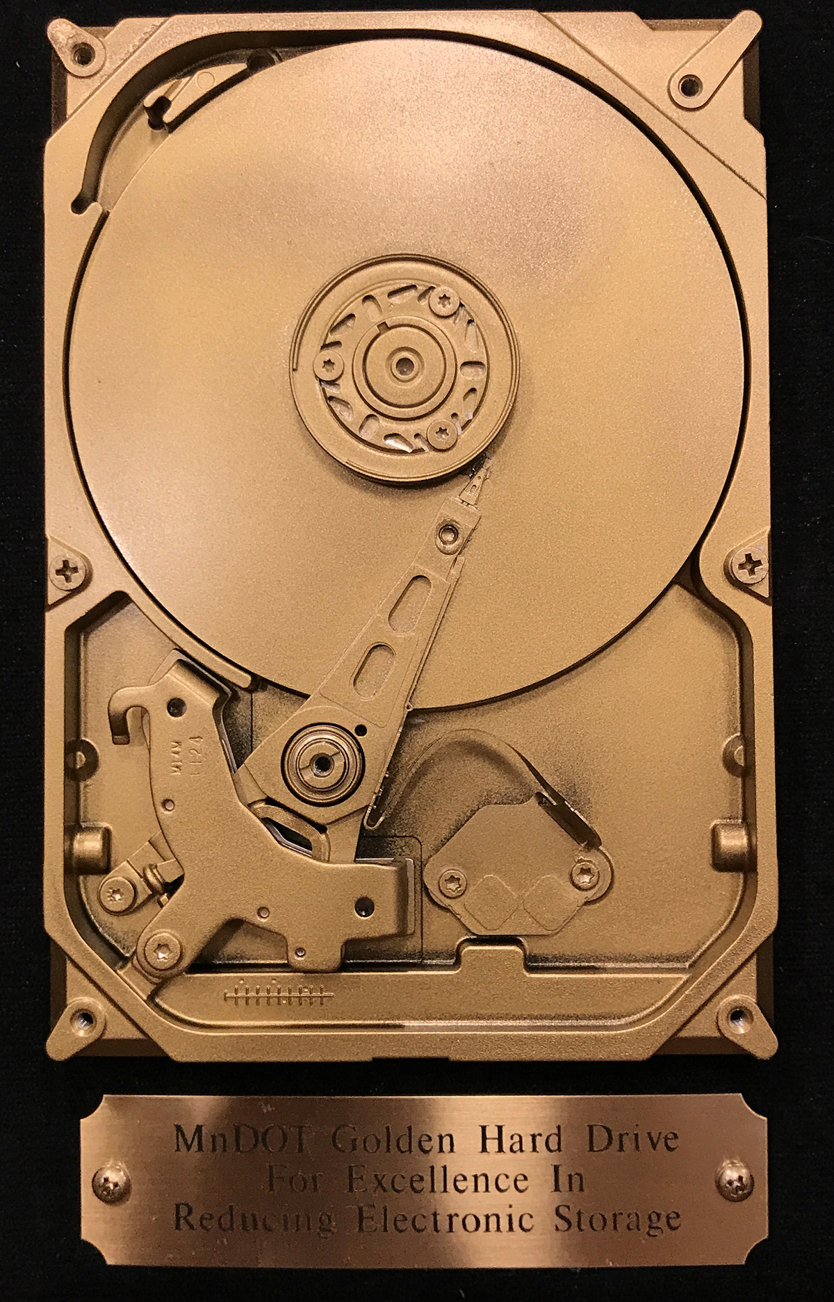 Photo: the golden hard drive award is an old computer hard drive painted gold. A brass plate underneath this hard drive says MnDOT golden hard drive for excellence in reduced electronic storage