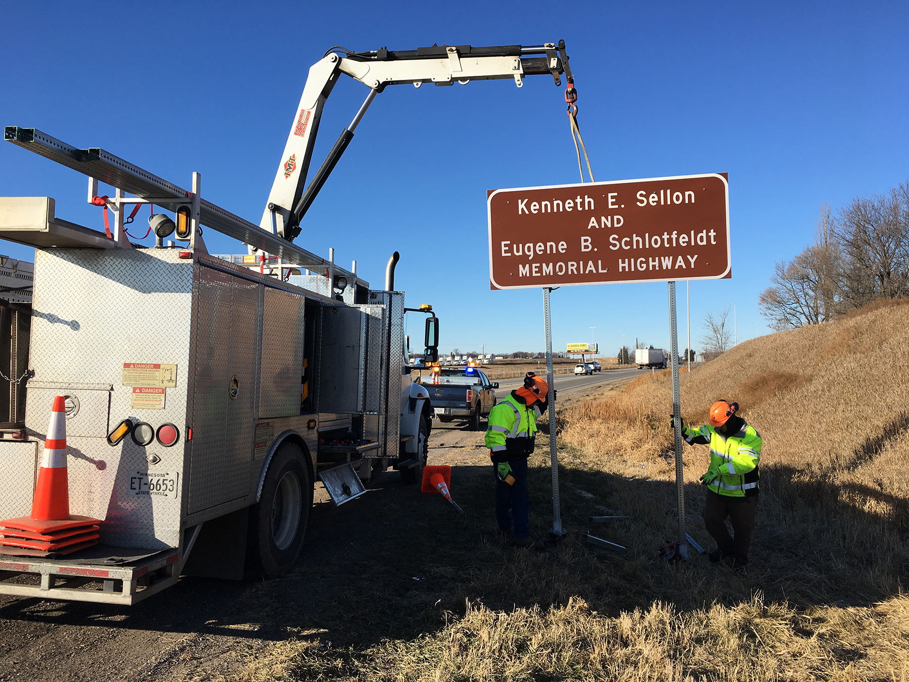 Photo: work crews install a sign on the side of Interstate 94. The sign says Kenneth E Sellon and Eugene B Schlotfeldt memorial highway