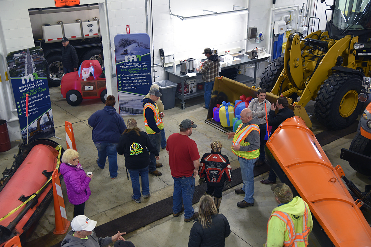 Photo: Overhead shot of people gathtered in the new Evansville truck station. MnDOT employees are wearing yellow safety vests.