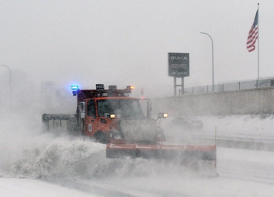 Photo: a snowplow kicks up a wake of snow while plowing on the highway