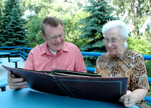 Man, woman looking at photo album