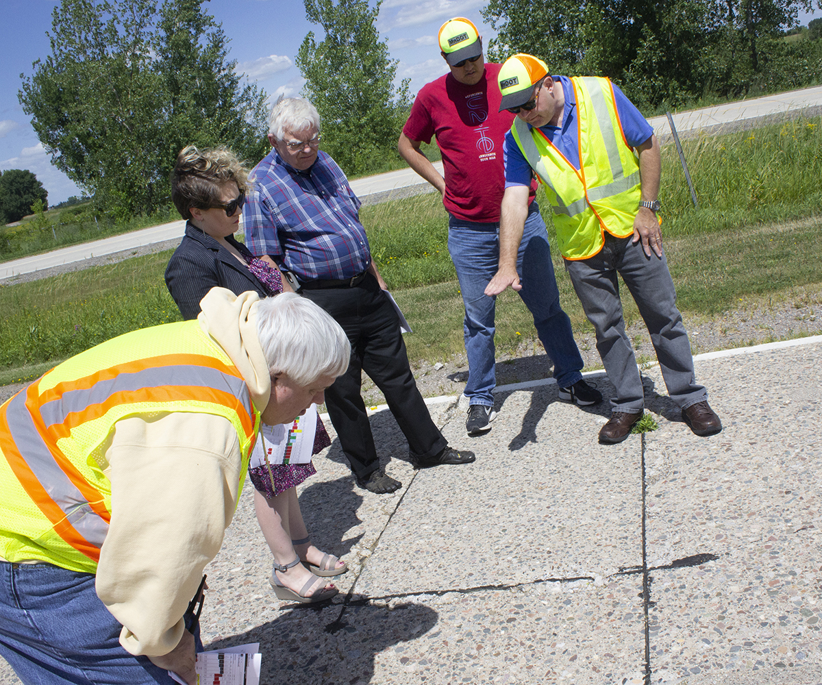 A man in a yellow safety vests gestures toward a section of concrete roadway, as others look at it too.