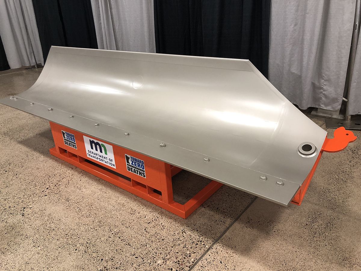 A very clean snowplow blade mounted on an orange metal stand.