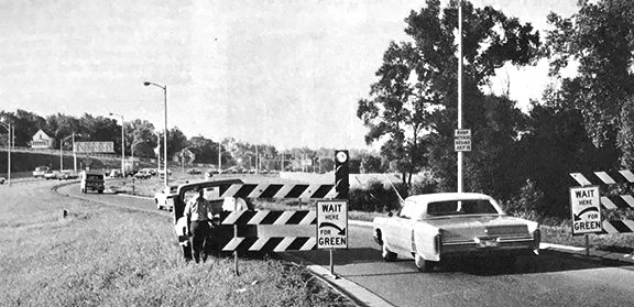 Black and white photograph showing an old car waiting to enter the freeway. The sign next to the car says wait here for green light
