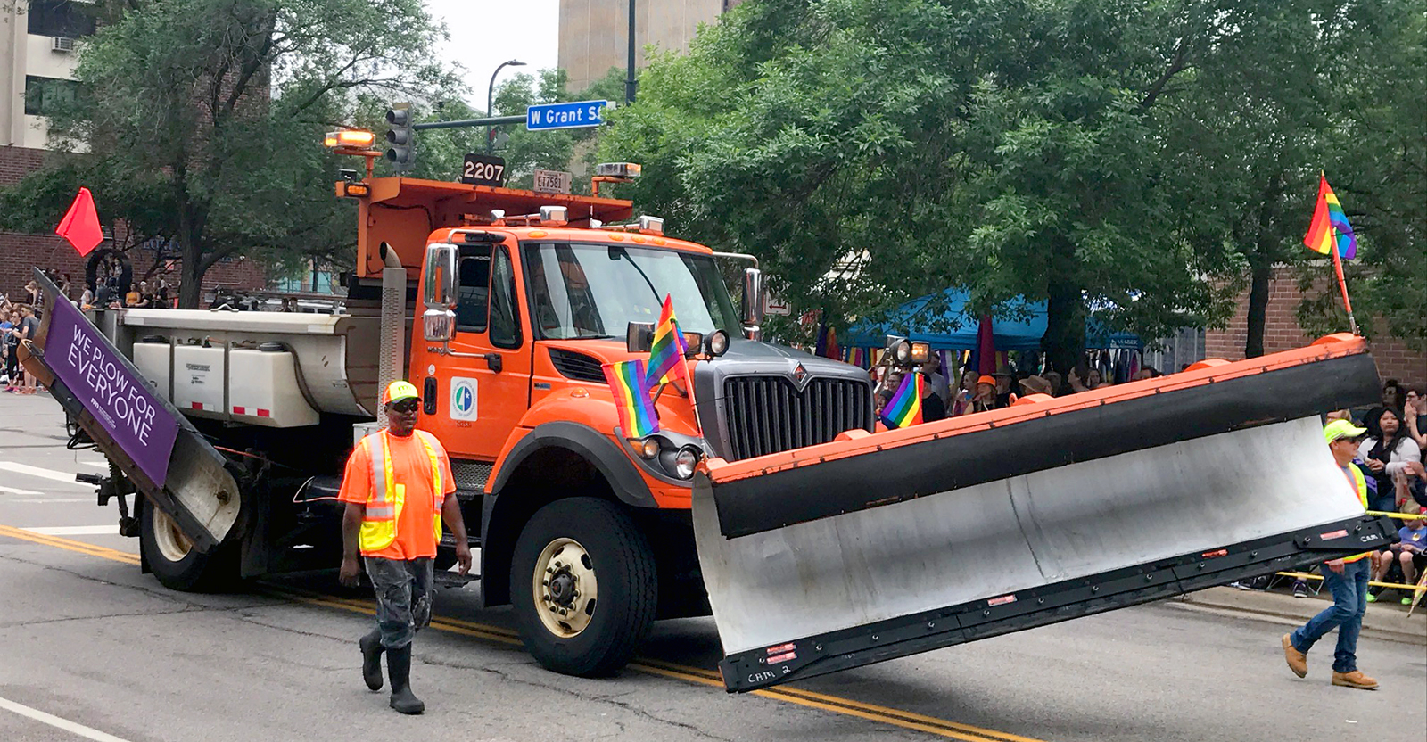 Picture of a plow truck driving through downtown Minneapolis. The side blade features a banner which reads we plow for everyone