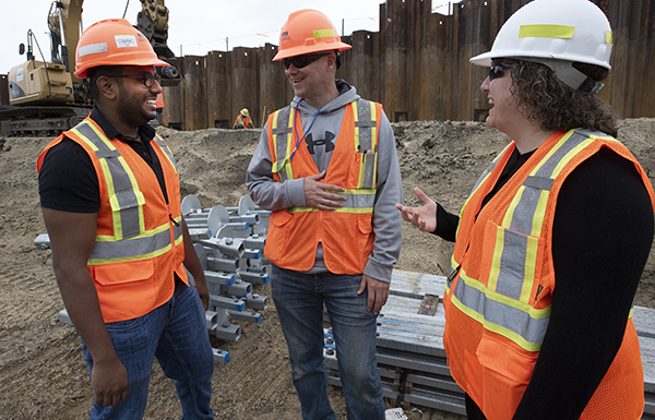 Picture of three people wearing safety vests and hard hats on a work site. Behind them are building materials being used in the project.