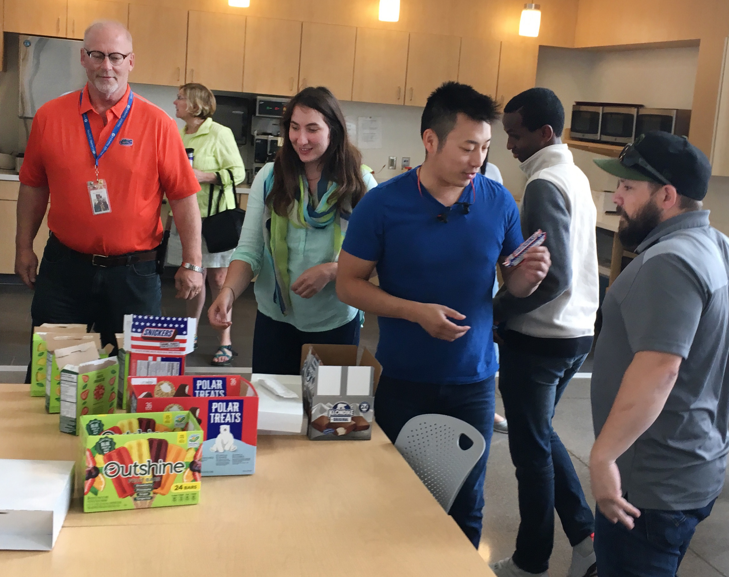 Employees in a break room are taking turns selecting which frozen treat they would like to eat.