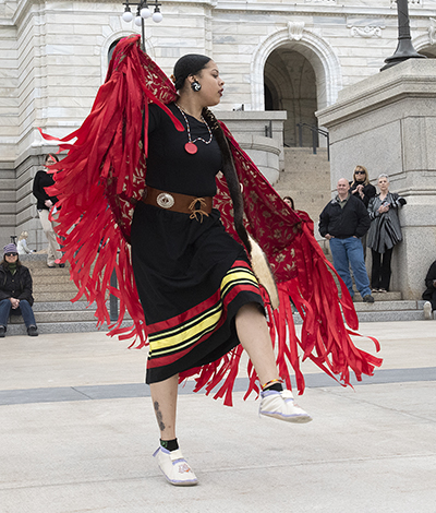A single dancer performs in front of the state capitol