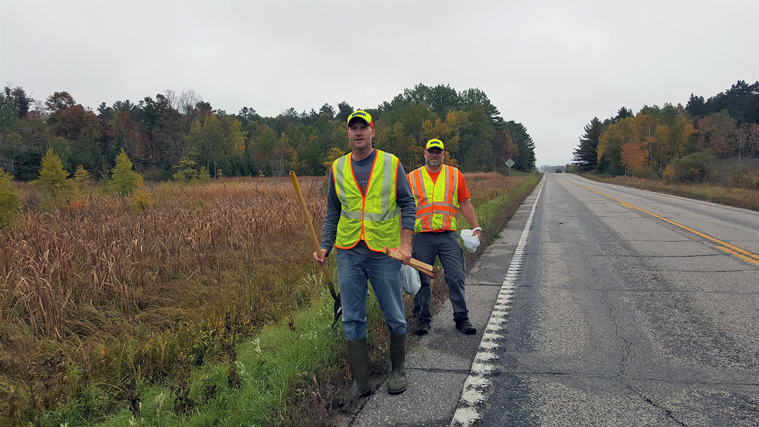 Photo: MnDOT crew members, standing near grass next to a road