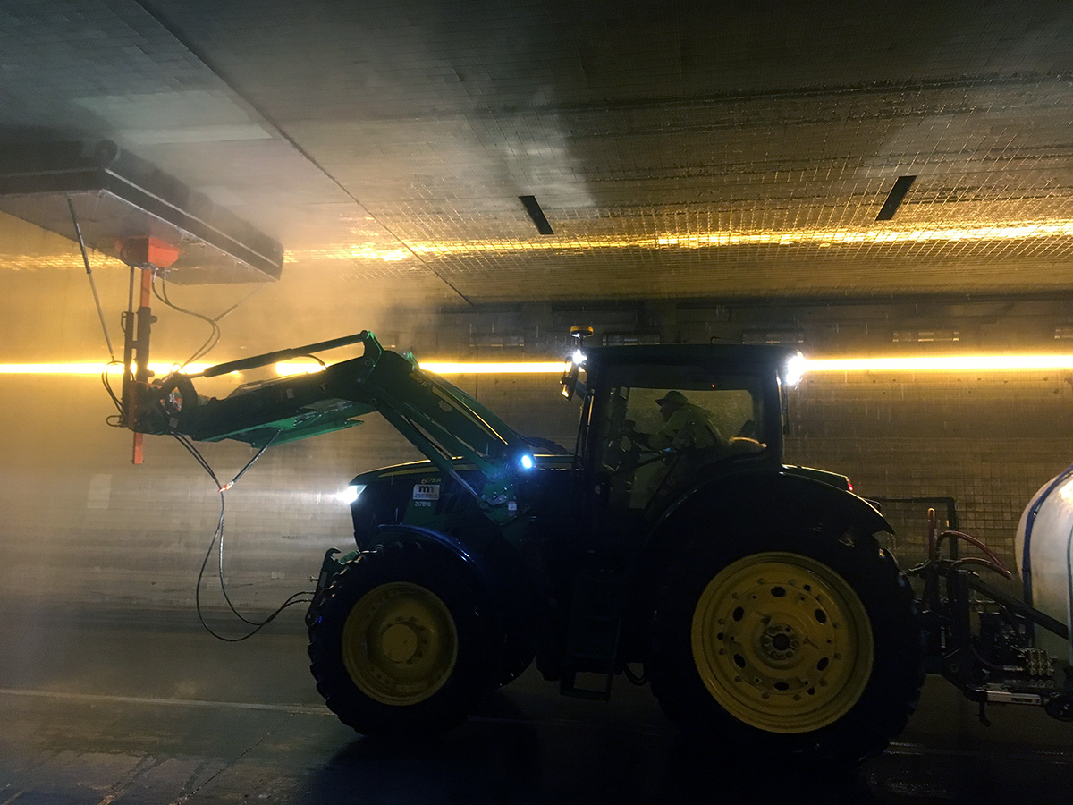 Photo: a John Deere tractor with a large spraying device mounted on the front arm, washing a tunnel ceiling