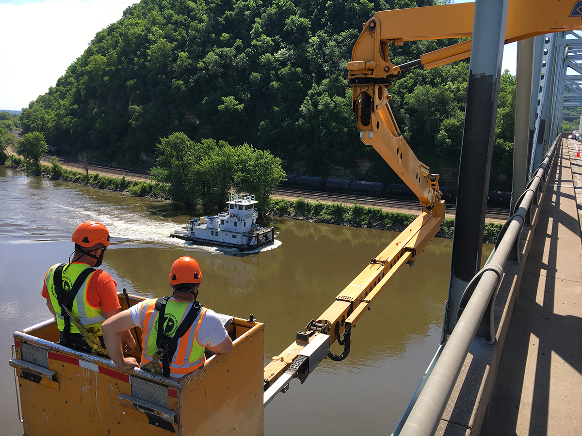 Photo: a work crew on a bridge, looking out over a river